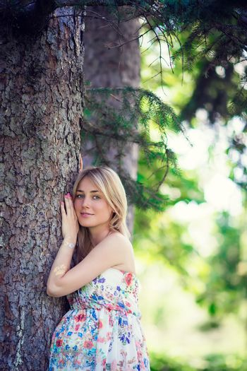Pregnant woman in outdoor park warm weather. Pregnancy concept - pregnant woman near tree over sunny summer background