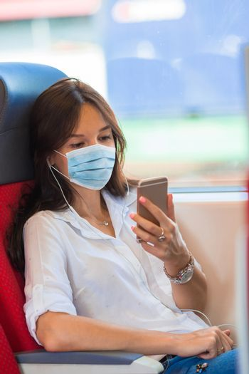Young woman traveling by train and wears a mask