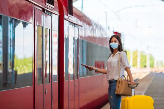 Woman wearing a mask for prevent virus with luggage on the platform travel by aeroexpress. Protection against Coronavirus and gripp