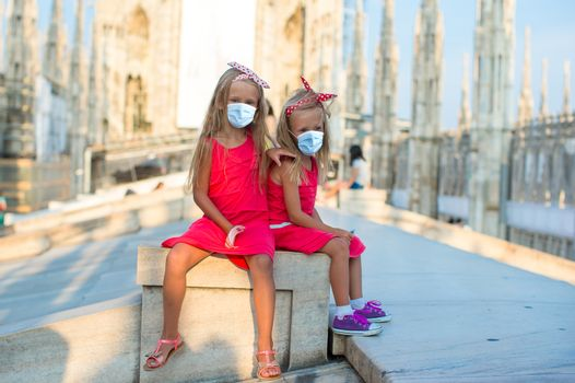 Adorable little girls wearing a mask for prevent virus on the rooftop of Duomo, Milan, Italy