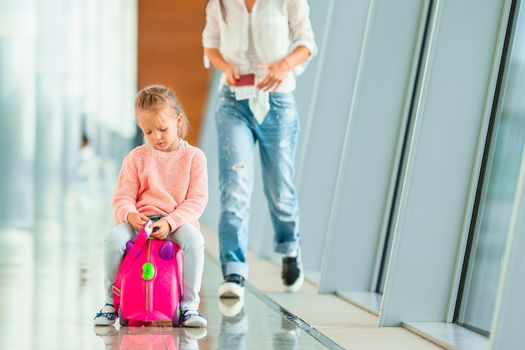 Happy mum and little girl with boarding pass at airport