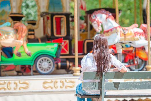 Beautiful woman near the carousel outdoors in Paris