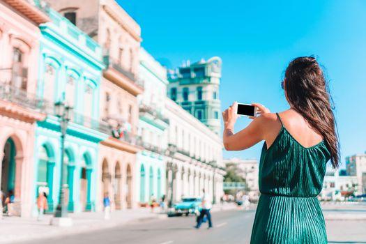 Tourist girl in popular area in Havana, Cuba. Young woman traveler smiling happy.