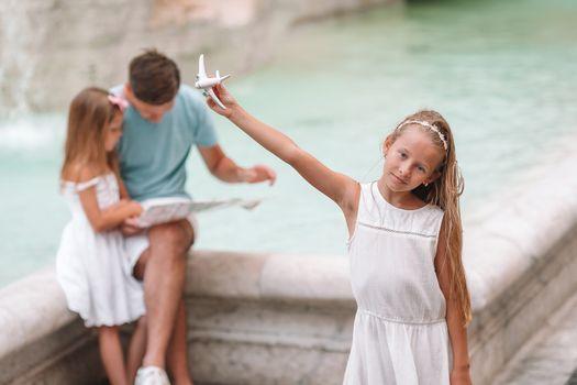 Family with touristic map near Fontana di Trevi, Rome, Italy.