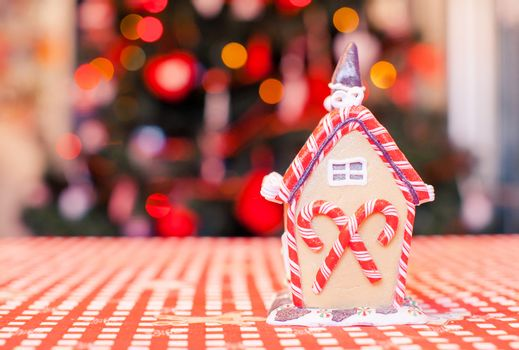 Gingerbread fairy house decorated by colorful candies on a background of bright Christmas tree with garland