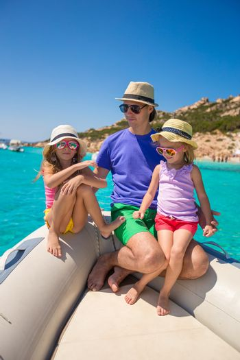 Young father with adorable girls resting on big boat
