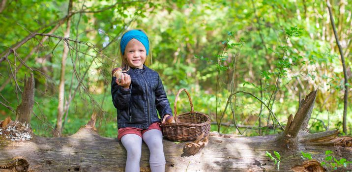 Little adorable girl gathering mushrooms in an autumn forest