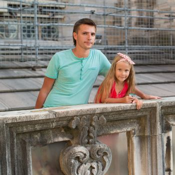 Adorable little girl with father on rooftop of Duomo, Milan, Italy
