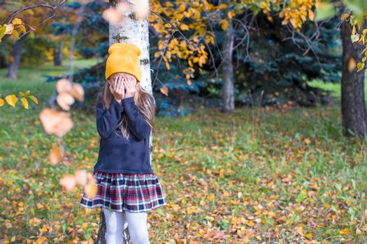 Little girl playing hide and seek in autumn forest
