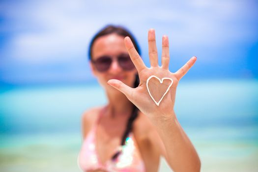 Closeup of girl's hand with heart on the palm painted by suncream