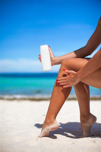 Woman apply cream on her smooth tanned legs
