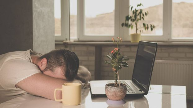 guy fell asleep at a desk with a laptop a flowerpot on a mountain table outside the window