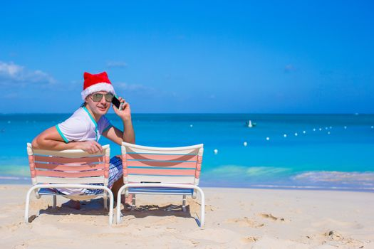 Young man in Christmas hat at beach chair