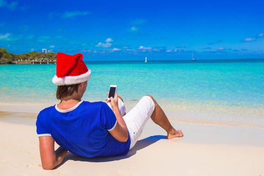 Young man in santa hat talking on phone at tropical beach