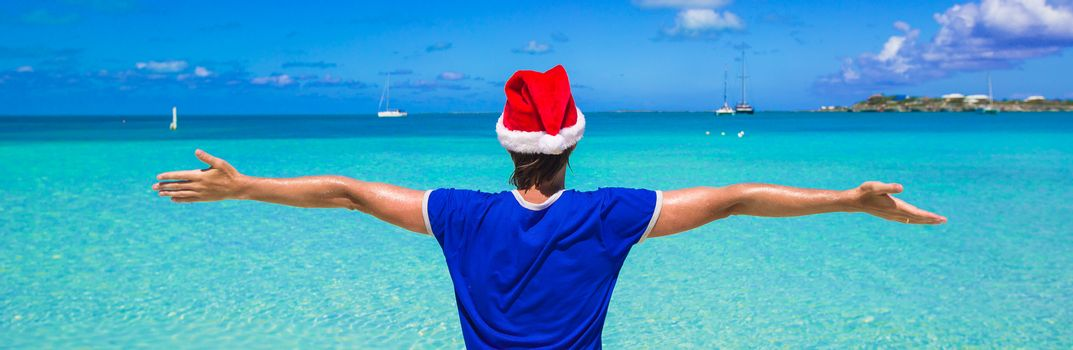 Young man in red santa hat on tropical beach