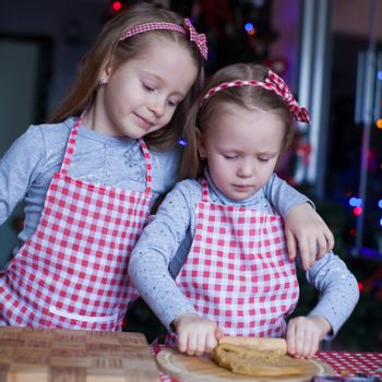 Adorable little girls in wore mittens baking Christmas gingerbread cookies