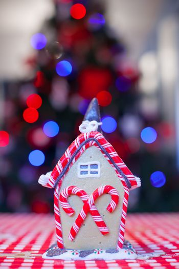 Gingerbread fairy house decorated with colorful candies of bright Christmas tree