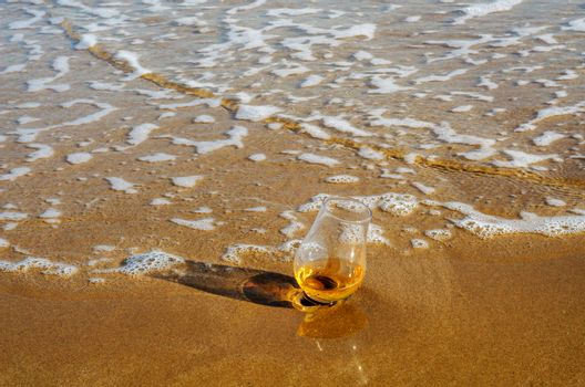 a glass of whiskey single malt on the sand washed by the waves,