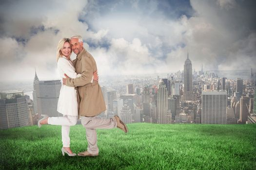 Composite image of happy couple posing in trench coats