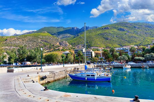 Fishing schooners and boats moored at the pier of the Gulf of the Ionian Sea amid the picturesque palm groves of the city park, the mountain slopes of Loutraki and the deep blue sky of Greece.