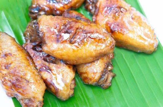 Chicken wings with cola sauce on green background