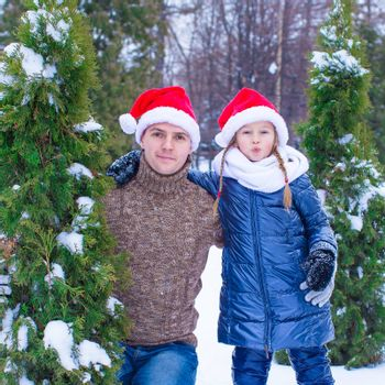 Happy family in Santa hats with christmas tree decorations outdoor