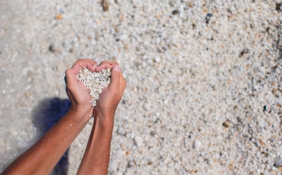 Hands in the form of heart with pebbles inside