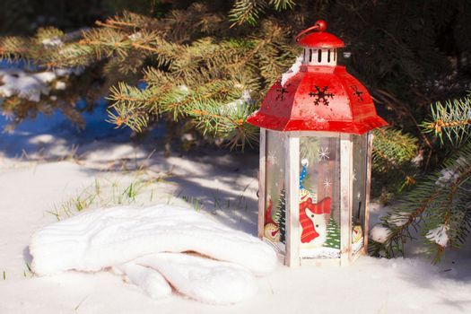Beautiful red fairytale lantern on white snow in forest