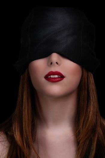 Low key shot of a gorgeous young woman with a black blindfold covering her eyes, isolated on black background. Beautiful blindfolded woman with red lipstick.