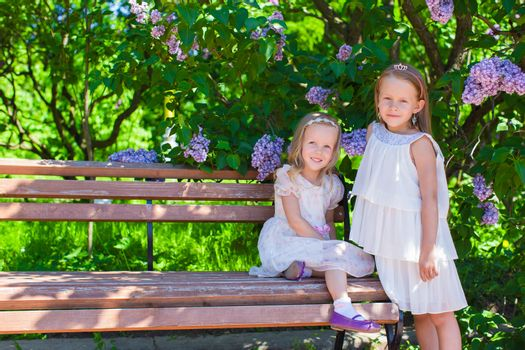 Little adorable girls in lush park in summer vacation
