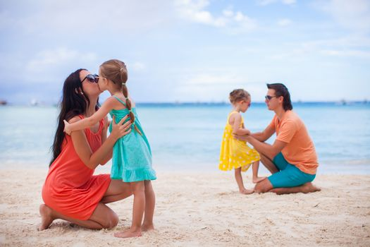 Happy family on white sandy beach