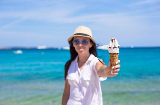 Adorable girl eating ice cream on a tropical beach