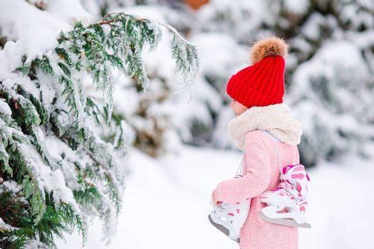 Beautiful little girl in red hat and white scarf with skates outdoor