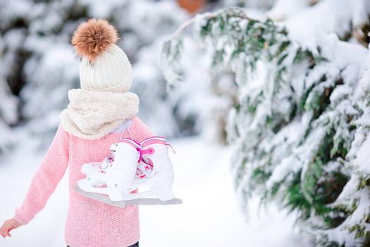 Adorable little girl going to skate in winter snow day outdoors