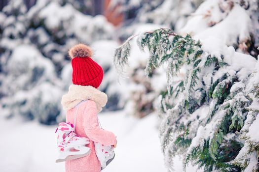Cute little girl in red hat going to skate in winter snow day outdoors