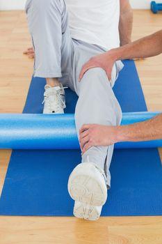 Physical therapist examining mans leg