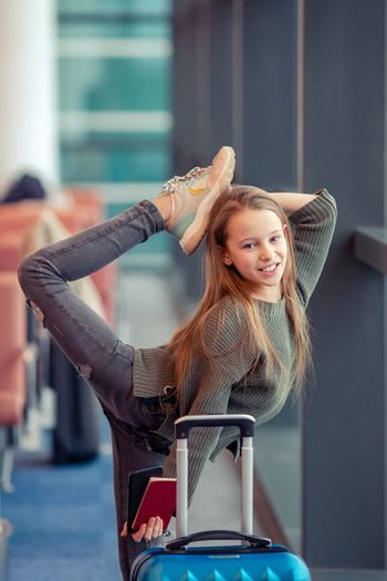 Little adorable kid in airport waiting for boarding indoors.