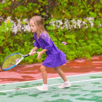 Little girl playing tennis on the court on vacation