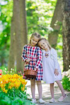 Little adorable girls walking in the lush garden of tulips
