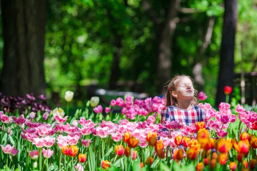 Little adorable girl in the lush garden of tulips
