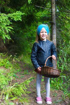 Little girl gathering mushrooms in autumn forest