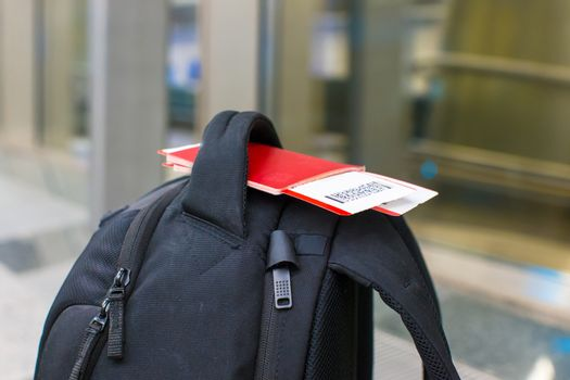 Closeup passports and boarding pass on backpack at airport