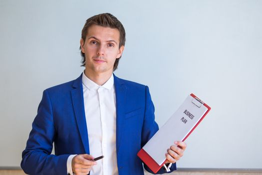 Young businessman with business plan and financial documents