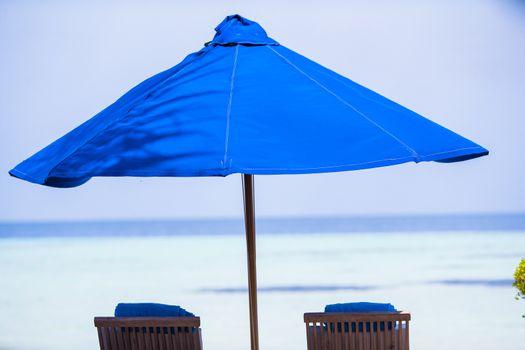 Blue umbrellas and sunbeds at tropical beach