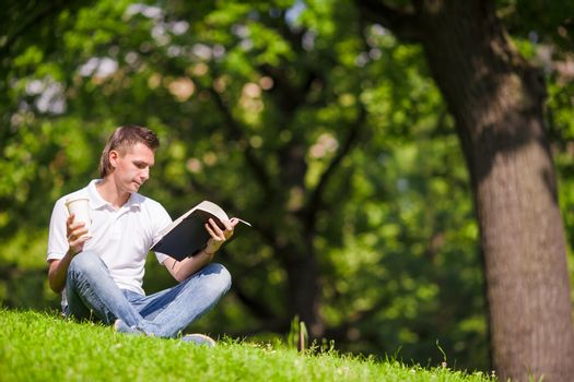 Clever man in park outside write down his thoughts in a notebook