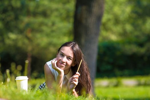Clever woman in park outside write down her thoughts in a notebook