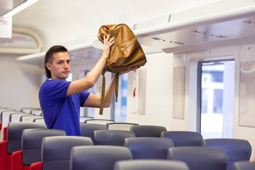 Young man putting luggage on the top shelf at aircraft
