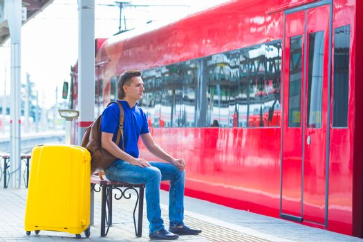 Young man with luggage on the platform waiting for aeroexpress