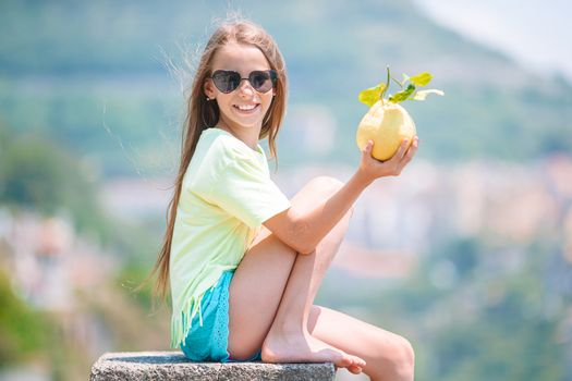 Big yellow lemon in hand in background of mediterranean sea and sky.