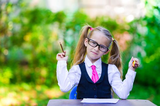 Portrait of clever little school girl in glasses with pencils outdoor